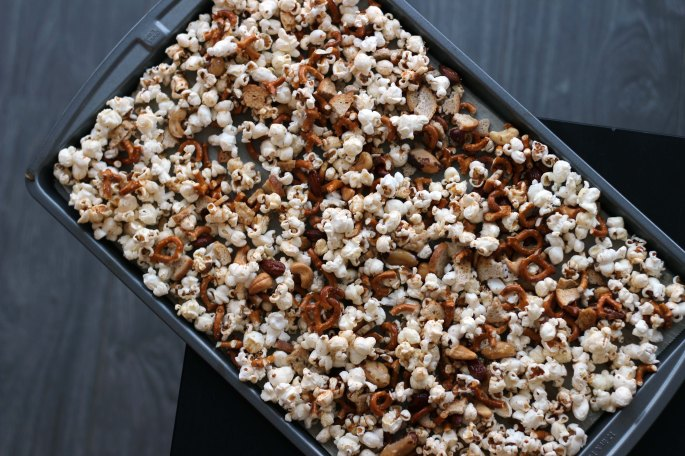 popcorn party mix on a baking sheet