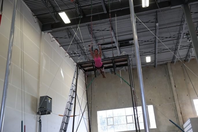 girl in pink shirt swinging on flying trapeze
