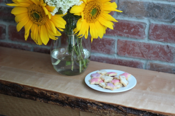 sunflowers and sugar cookies on a plate